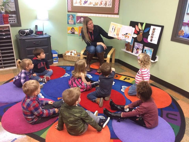 A preschool teacher reads a book to a group of children sitting on carpet circles.