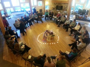 A large group of women sitting in a circle of chairs with a ring of tea lights in the center.